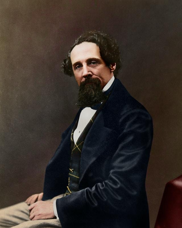 A black-and-white image to have been colourised, showing a 47-year-old Dickens with tanned skin and an ostentatious waistcoat