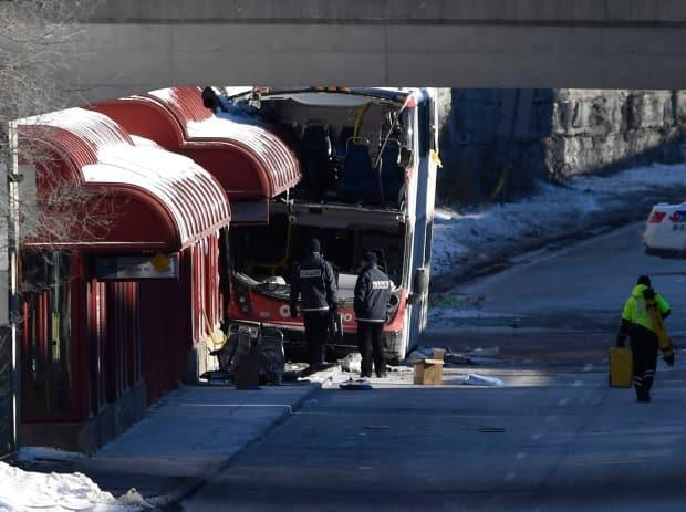 Transport Canada officials look at the scene where double-decker 8155 struck a transit shelter at Westboro Station in Ottawa in January 2019. (Justin Tang/Canadian Press - image credit)