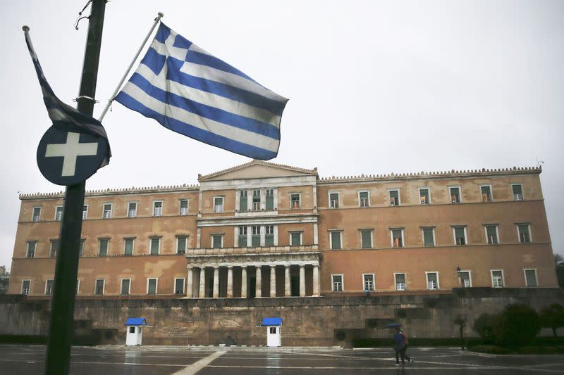 A Greek national flag flutters in front of the parliament building during heavy rainfall in Athens