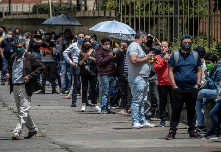 People queue outside a store in the Colombian capital Bogota as the World Health Organization warned of new coronavirus outbreaks