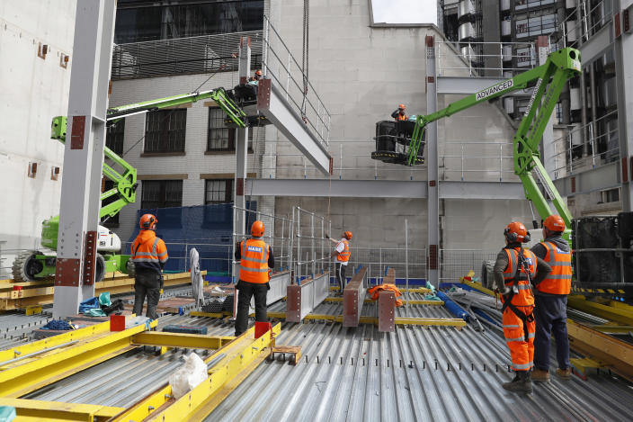Construction workers lift a Steele beam into position at the 8 Bishopsgate development in London, Thursday, April 1, 2021. When the pandemic struck, about 540,000 workers vanished from London's financial hub almost overnight. Developers of 8 Bishopsgate, are confident that when construction ends late next year, workers and firms will return to fill all 50 floors of the gleaming new office space. (AP Photo/Alastair Grant)