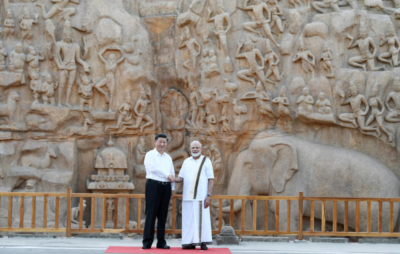 In this Friday, Oct. 11, 2019, handout photo provided by the Indian Prime Minister's Office, Chinese President Xi Jinping and Indian Prime Minister Narendra Modi shake hands at Arjuna's Penance in Mamallapuram, India. Xi on Friday met with Modi at a time of tensions over Beijing's support for Pakistan in opposing India's downgrading of Kashmir's semi-autonomy and continuing restrictions on the disputed region. (Indian Prime Minister's Office via AP)