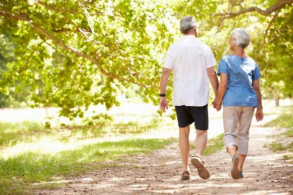 Man and woman in their 60s walking down a path holding hands.