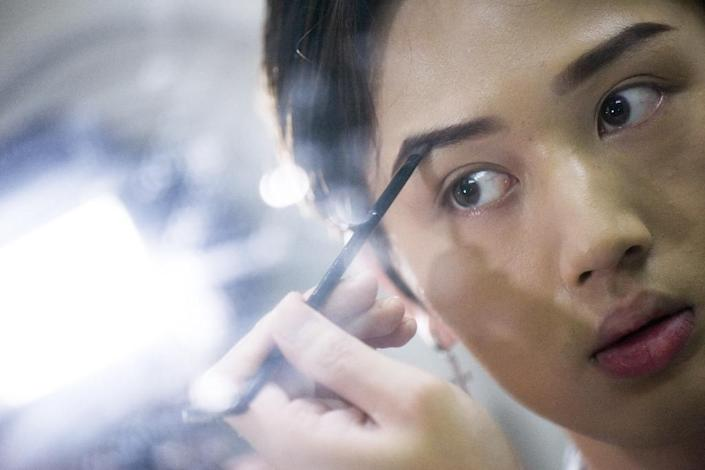 Lan Haoyi doing make up before recording video at his home in Beijing (AFP Photo/WANG ZHAO)
