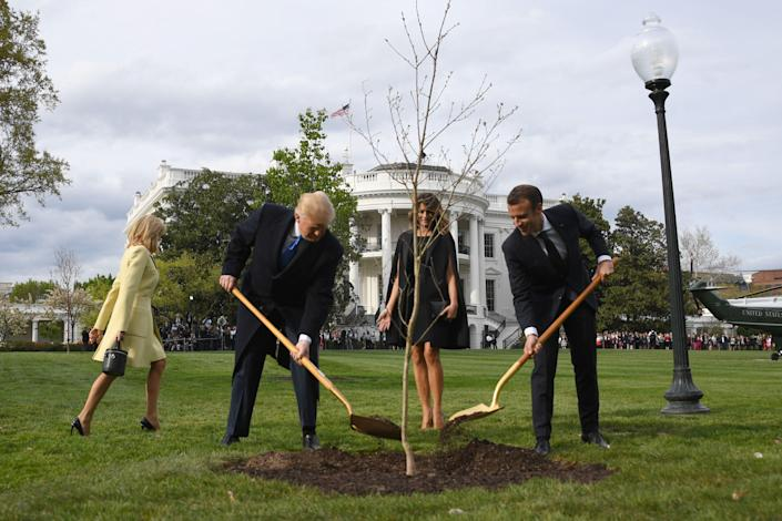 US President Donald Trump and First Lady Melania Trump participate in a tree planting ceremony with French President Emmanuel Macron and his wife Brigitte Macron on the South Lawn of the White House in Washington, DC, on April 23, 2018. The tree comes from Belleau Woods, where, in June 1918, some 9,000 US Marines died in the Belleau Wood battle during World War I. / AFP PHOTO / JIM WATSONJIM WATSON/AFP/Getty Images ORIG FILE ID: AFP_1497JE