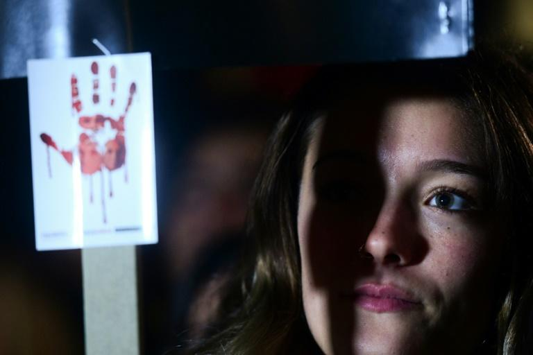 A protester holds a sign outside of parliament in Malta, where the latest twist in the journalist's murder case sparked outrage