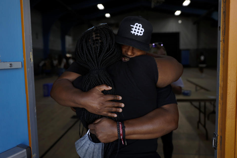 Think Watts Foundation's Sheldon Lewis, facing camera, hugs volunteer Tanya Dorsey after attending a community event held to give out free food to tenants living in the Nickerson Gardens housing project in the Watts neighborhood of Los Angeles, Wednesday, June 10, 2020. (AP Photo/Jae C. Hong)