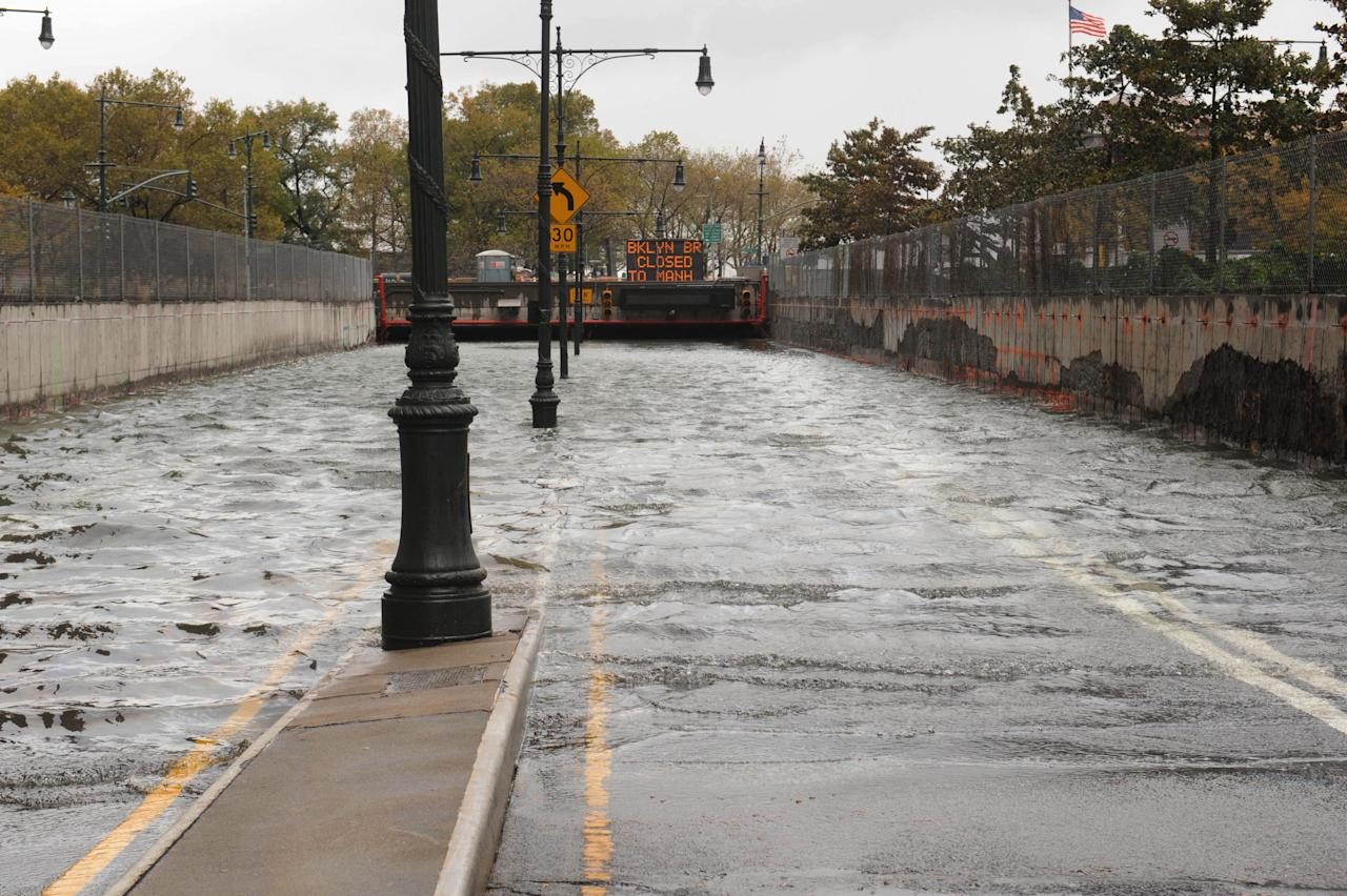 CORRECTS NAME OF FLOODED AREA TO BATTERY PARK UNDERPASS, INSTEAD OF BROOKLYN BATTERY TUNNEL - Water reaches street level at the West Street entrance to the Battery Park Underpass, Tuesday, Oct. 30, 2012, in New York. Sandy, the storm that made landfall Monday, caused multiple fatalities, halted mass transit and cut power to more than 6 million homes and businesses. (AP Photo/ Louis Lanzano)