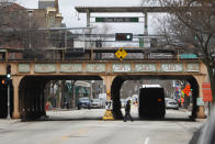 A man walks under the Chicago Transit Authority train station in the Village of Oak Park, Ill., Friday, March 20, 2020. There are at least three confirmed cases of COVID-19 in Oak Park, just nine miles from downtown Chicago, where the mayor has ordered residents to shelter in place. With so few tests available, surely there are others, says Tom Powers, spokesman for the village of about 52,000 in a metropolitan area with millions. (AP Photo/Charles Rex Arbogast)