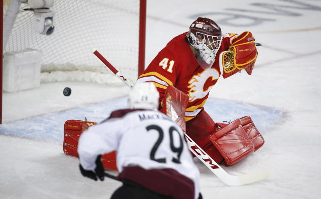 Colorado Avalanche center Nathan MacKinnon (29) scores on Calgary Flames goaltender Mike Smith (41) during overtime of an NHL hockey playoff game in Calgary, Alberta, Saturday, April 13, 2019. (Jeff McIntosh/The Canadian Press via AP)
