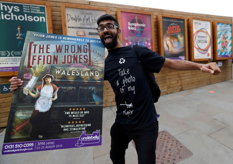 FILE PHOTO: A man holding a poster is seen in front of flyers advertising shows at the Fringe in Edinburgh