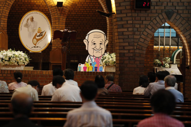 People pray at the Assumption Cathedral as a caricature of Pope Francis is placed alongside in Bangkok, Thailand, Tuesday, Nov. 19, 2019. Pope Francis arrives in Thailand on Wednesday for the first visit here by the head of the Roman Catholic Church since St. John Paul II in 1984. (AP Photo/Manish Swarup)