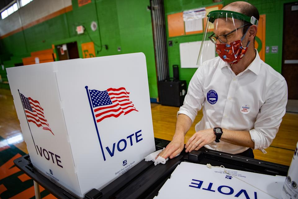 DETROIT, MI - AUGUST 4: Reuben Levy, volunteer, disinfect a voting booth after voters cast their ballots at a polling station inside Frederick Douglass Academy during Michigan Primary in Detroit, Michigan on Tuesday, August 4, 2020. (Photo by Salwan Georges/The Washington Post via Getty Images)