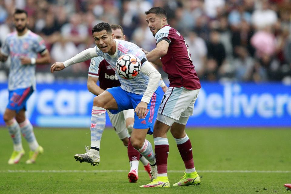Manchester United's Cristiano Ronaldo, left, goes for the ball as West Ham's Pablo Fornals tries to stop him during the English Premier League soccer match between West Ham United and Manchester United at the London Stadium in London, England, Sunday, Sept. 19, 2021. (AP Photo/Ian Walton)