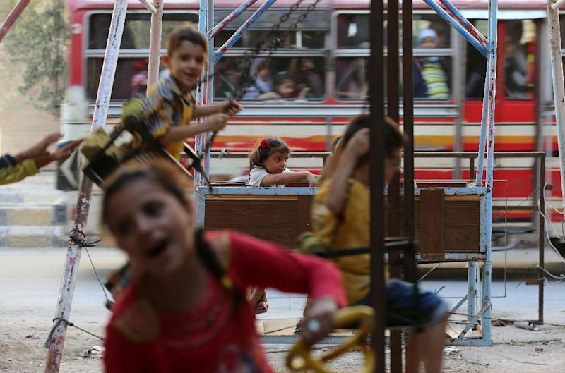 Syrian children play on swings in Arbin, on the outskirts of the capital Damascus, as they celebrate the Muslim Eid al-Adha holiday on September 13, 2016 (AFP Photo/Amer Almohibany)
