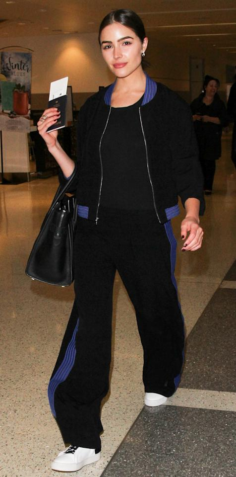 The beauty queen prepared for takeoff at LAX in a chic black tracksuit by ALEXIS with royal blue piping and a pair of black-laced white leather sneakers.