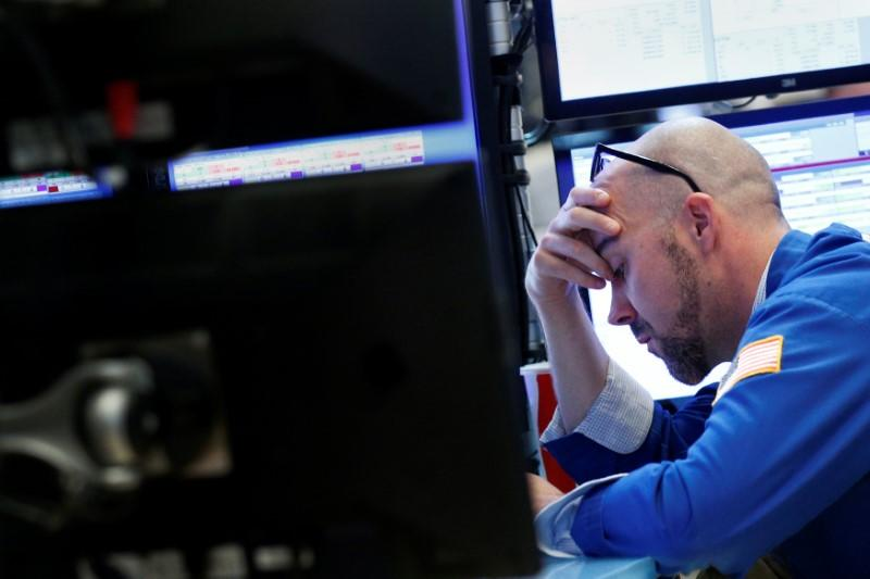 A trader works at his post on the floor of the NYSE in New York City