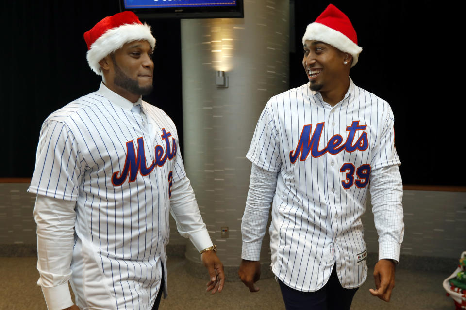 Robinson Cano, left, and Edwin Diaz wear Santa hats as they arrive to participate in New York Mets annual Kids Holiday Party, at CitiField, in New York, Tuesday, Dec. 4, 2018. (AP Photo/Richard Drew)