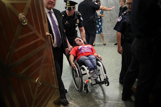<p>U.S. Capitol Police remove a protester in a wheel chair from a Senate Finance Committee hearing about the proposed Graham-Cassidy Healthcare Bill in the Dirksen Senate Office Building on Capitol Hill September 25, 2017 in Washington, DC. Demonstrators disrupted the hearing to protest the legislation, the next in a series of Republican proposals to replace the Affordable Care Act, also called Obamacare. (Photo: Chip Somodevilla/Getty Images) </p>