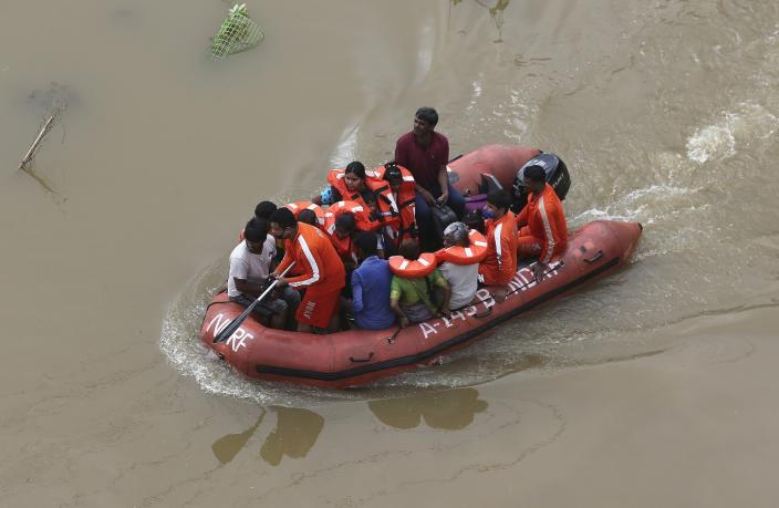 National Disaster Response Force (NDRF) personnel rescue people from the flood water after heavy rainfall in Hyderabad, India, India, Wednesday, Oct. 14, 2020. (AP Photo/Mahesh Kumar A.)