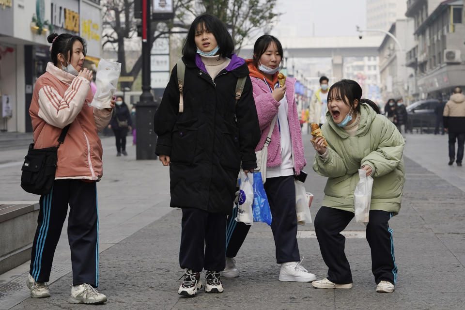 Young girls enjoy a light moment as they visit a popular shopping street in Wuhan in central China's Hubei province on Tuesday, Jan. 26, 2021. The central Chinese city of Wuhan, where the coronavirus was first detected, has largely returned to normal but is on heightened alert against a resurgence as China battles outbreaks elsewhere in the country. (AP Photo/Ng Han Guan)
