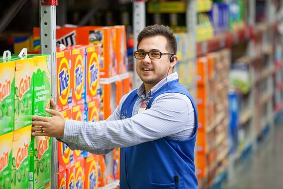 A Sam's Club employee stacking boxed detergent in a store
