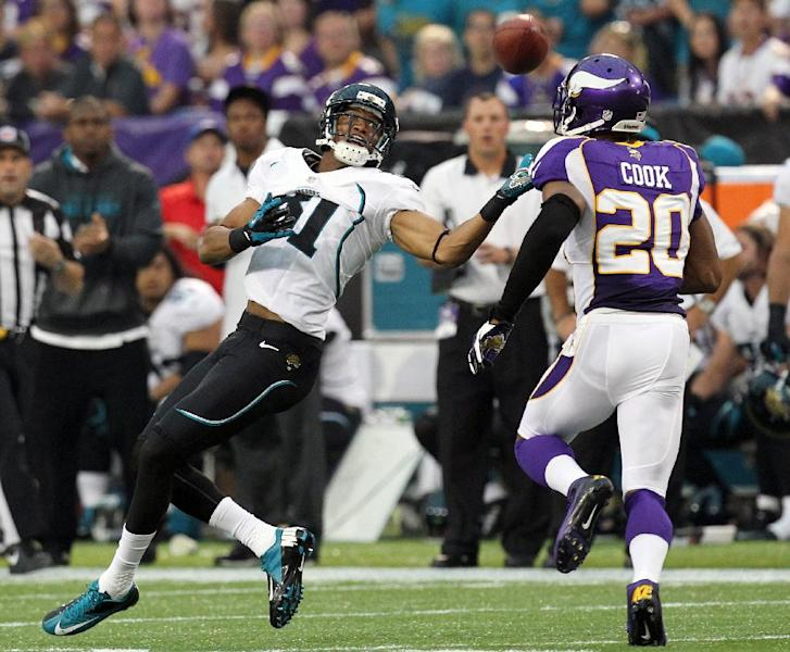 Jacksonville Jaguars wide receiver Laurent Robinson, left, makes a reception over Minnesota Vikings cornerback Chris Cook, right, during the first half of an NFL football game on Sunday, Sept. 9, 2012, in Minneapolis. (AP Photo/Genevieve Ross)