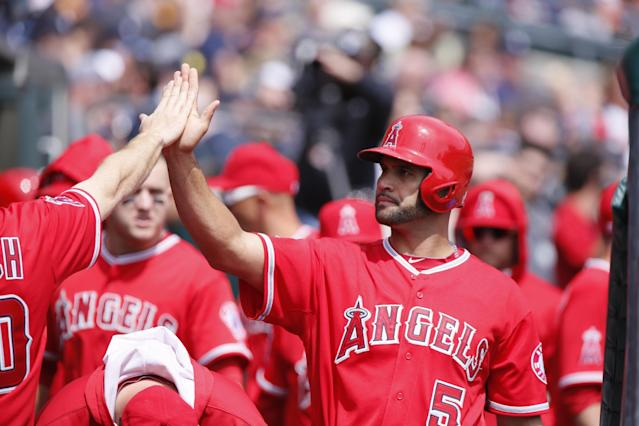 Los Angeles Angels' Albert Pujols receives a high-five in the dugout after scoring in the first inning of a baseball game against the Detroit Tigers Sunday, April 20, 2014, in Detroit. (AP Photo/Duane Burleson)