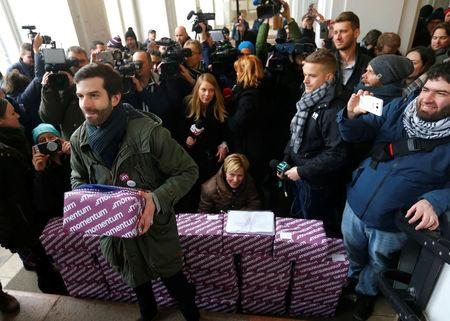 Fekete-Gyor, leader of political movement Momentum holds up one of the  boxes containing over 266,000 signatures of Budapest voters who want a referendum on Budapest's bid to host the 2024 Summer Olympics in Budapest