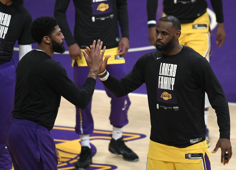 LeBron James #23 of the Los Angeles Lakers and Anthony Davis #3 high five before the game against the Phoenix Suns during game six of the Western Conference first round series at Staples Center on June 03, 2021 in Los Angeles, California. (Photo by Harry How/Getty Images) NOTE TO USER: User expressly acknowledges and agrees that, by downloading and or using this photograph, User is consenting to the terms and conditions of the Getty Images License Agreement.