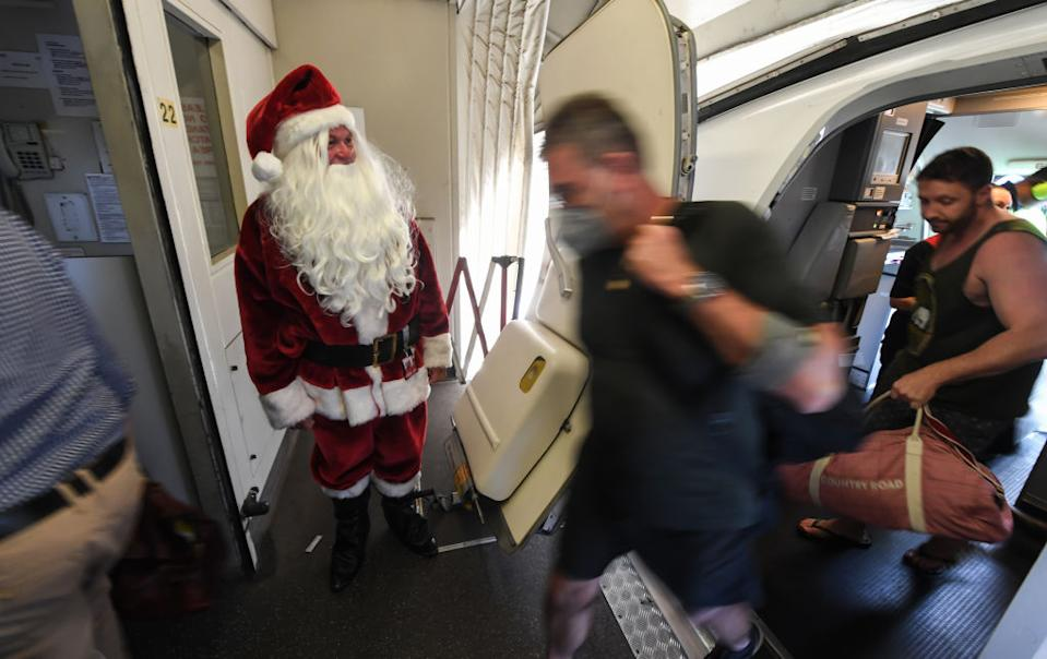 Qantas Captain Steve Anderson dressed as Santa Claus greets passengers as they disembark his Boeing 737 aircraft at Brisbane Airport after arrival on December 16, 2020 in Brisbane, Australia.