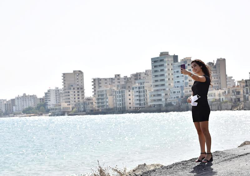 A woman takes a selfie inside an area fenced off by the Turkish military since 1974 in the abandoned coastal area of Varosha.