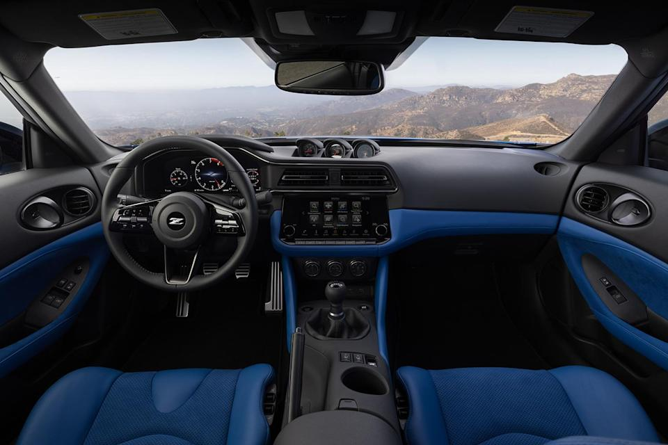 The interior of the new 2023 Nissan Z, featuring analog pod gauges, a new digital meter display and even a good ol' handbrake. The sports car was unveiled in August 2021.