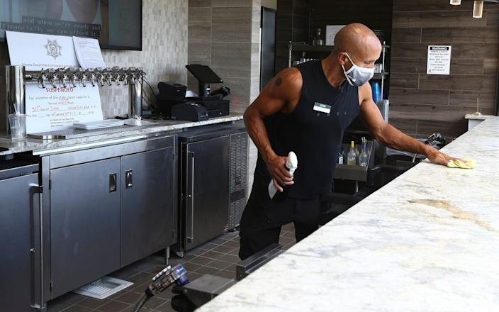 A worker at a health club in Phoenix keeps the bar clean, but facilities in Arizona could soon be closing again - AP