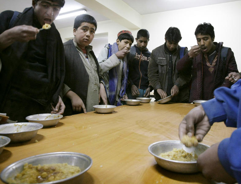 In this Thursday, Feb. 21, 2013 photo, Afghan street children take their lunch meal at the Afghanistan's Children-A New Approach (ASCHIANA) center in Kabul, Afghanistan. The impending withdrawal of U.S. and other foreign combat forces from Afghanistan means more than a loss of firepower. International aid is also on the decline because of donor fatigue and fears of deteriorating security after nearly 12 years of war. Worried about losing hard-won gains, aid organizations are racing to finish projects or find new sources of funding to provide basic services that the weak central government has been unable to deliver.(AP Photo/Musadeq Sadeq)