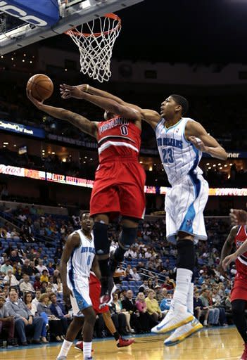 Portland Trail Blazers point guard Damian Lillard (0) goes to the basket against New Orleans Hornets power forward Anthony Davis (23) in the first half of an NBA basketball game in New Orleans Sunday March 10, 2013. (AP Photo/Gerald Herbert)