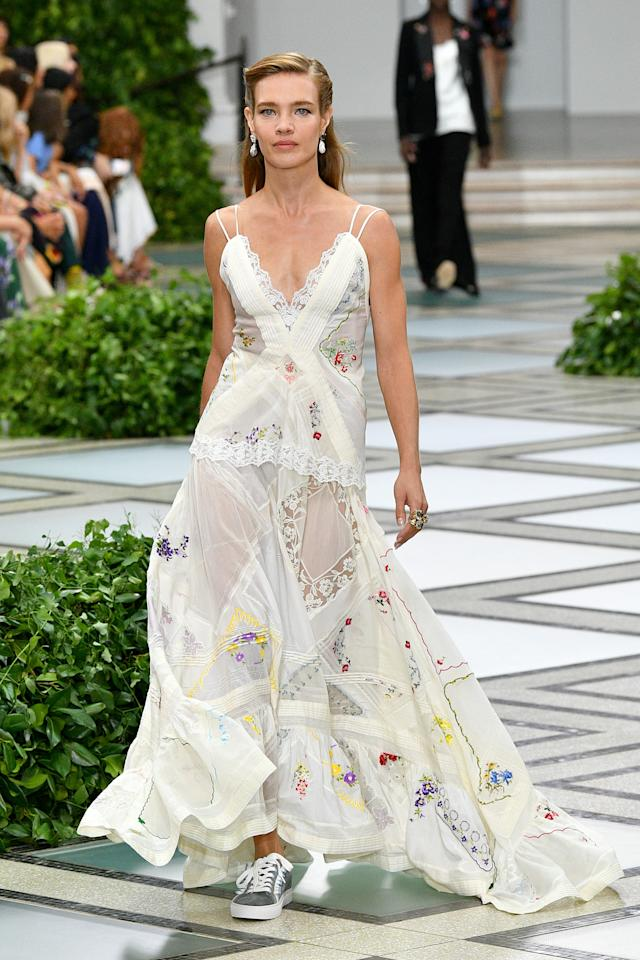 """<p>Set in the Brooklyn Museum, Tory Burch's spring summer 2020 show borrowed the elegance and grace of Princess Diana. Guests were greeted with a gorgeous morning feast of scones, tarts, and crepe cakes topped with raspberries in whimsical cabbage """"lettuce-ware"""" (also by Tory Burch). The classic English breakfast.</p> <p>The show itself was practical giving everyone the chance to embody a little bit of Princess Di. There were dresses with balloon sleeves and dramatic necktie blouses, suiting was peppered in, and polka dots were used tastefully. This dress pieced together with various embroidered handkerchiefs combined the ease of Princess Diana's style with Burch's own take of the 80s. It's simple but upon closer inspection the details (lined up seams, touches of lace, and cascading hem) all contribute to the success of a dress that finds the balance between throw-on-and-go dressing and captivating statement pieces.</p> <p>All guests left the show with an embroidered kerchief and (probably) a scone for the road.</p>"""