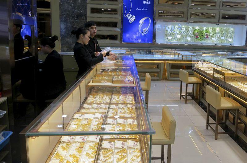 Staff wait for customers inside an empty gold and jewellery store in Shenzhen's Shuibei district