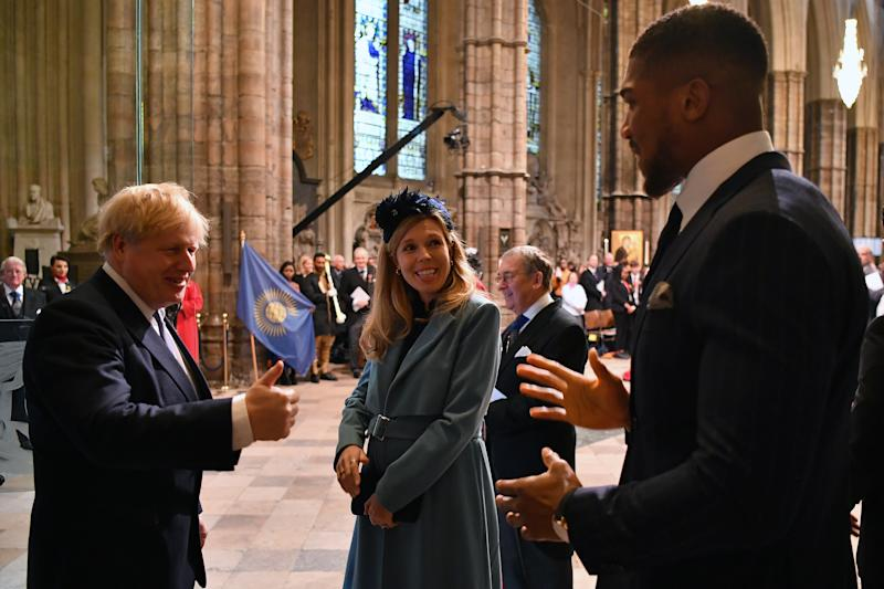 Britain's Prime Minister Boris Johnson and his fiancee partner Carrie Symonds talks with British boxer Anthony Joshua as she leaves after attending the annual Commonwealth Service at Westminster Abbey in London on March 09, 2020. - Britain's Queen Elizabeth II has been the Head of the Commonwealth throughout her reign. Organised by the Royal Commonwealth Society, the Service is the largest annual inter-faith gathering in the United Kingdom. (Photo by Ben STANSALL / POOL / AFP) (Photo by BEN STANSALL/POOL/AFP via Getty Images)