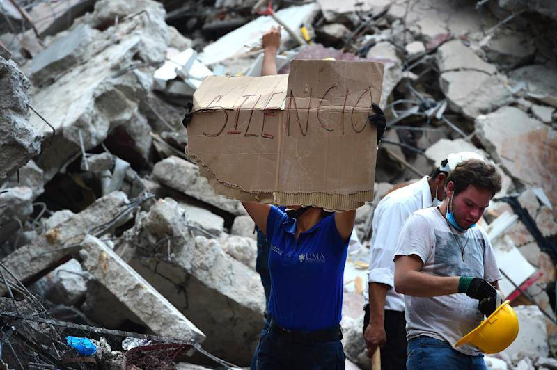 Rescuers searching for survivors buried under the rubble ask for silence to help locate those who may be trapped.
