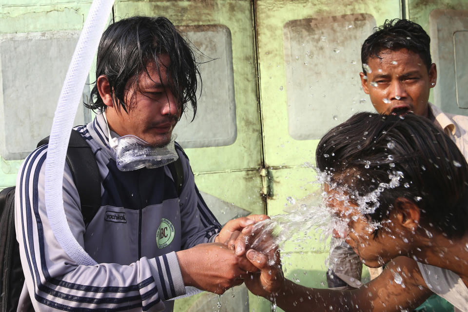People rinse their faces with water after tear gas was used to disperse a protest in Mandalay, Myanmar on Saturday, Feb. 20, 2021.Security forces in Myanmar ratcheted up their pressure against anti-coup protesters Saturday, using water cannons, tear gas, slingshots and rubber bullets against demonstrators and striking dock workers in Mandalay, the nation's second-largest city. (AP Photos)