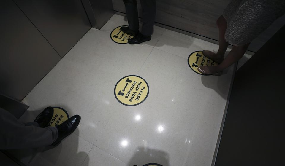 Stickers mark the spot for people to stand in a lift to maintain social distance amid the coronavirus pandemic. Photo: Xiaomei Chen