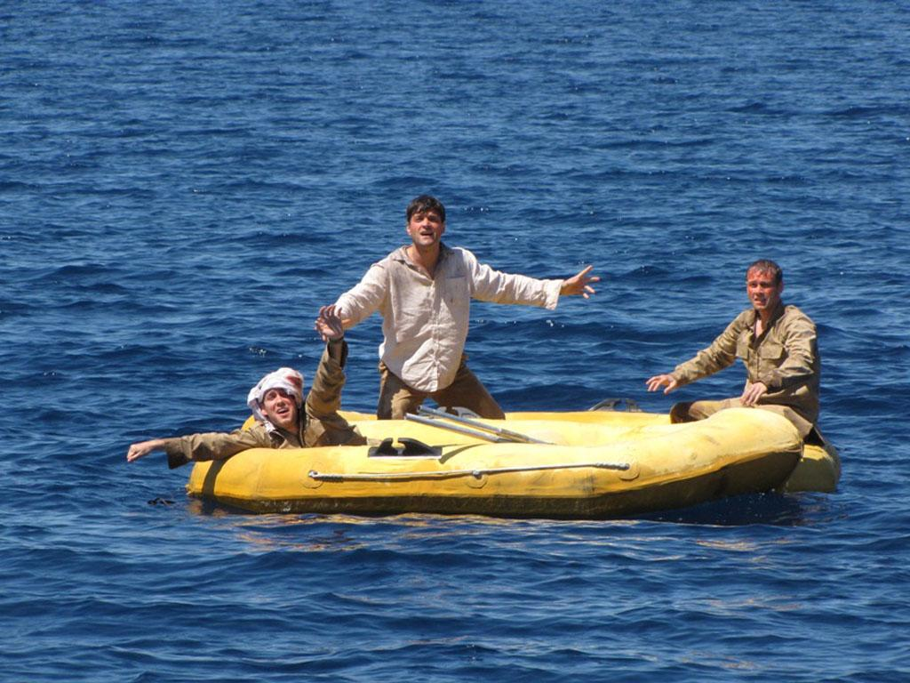 Mac (AARON TAYLOR), Phil (RAY BURNS) and Louis (MICHAEL KOLTES) spot a plane in the distance. Adrift: 47 Days with Sharks