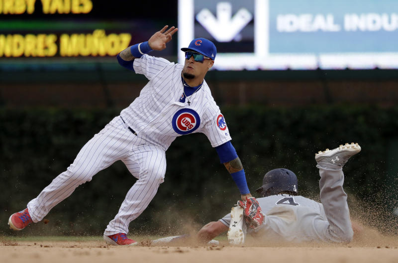 Chicago Cubs shortstop Javier Baez, left, tags out San Diego Padres' Wil Myers at second during the ninth inning of a baseball game in Chicago, Saturday, July 20, 2019. The Cubs won 6-5. (AP Photo/Nam Y. Huh)