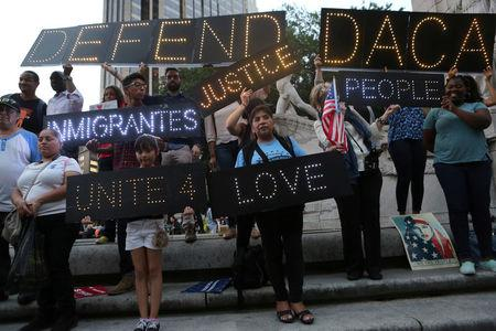 FILE PHOTO: People hold signs against U.S. President Donald Trump's proposed end of the DACA program that protects immigrant children from deportation at a protest in New York City, U.S., August 30, 2017. REUTERS/Joe Penney