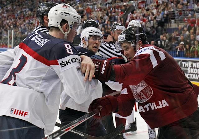 USA defender Jacob Trouba, left, fights with Latvia defender Kristaps Sotnieks during the Group B preliminary round match between USA and Latvia at the Ice Hockey World Championship in Minsk, Belarus, Thursday, May 15, 2014. (AP Photo/Darko Bandic)