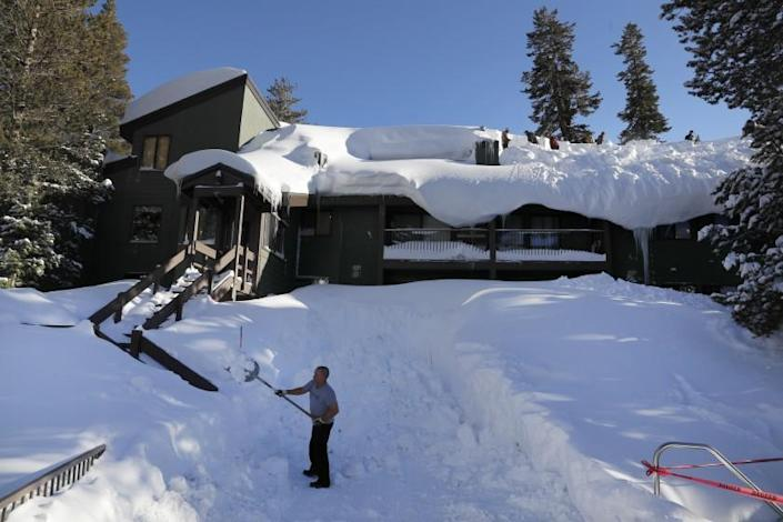MAMMOTH LAKES, CALIF. -- WEDNESDAY, FEBRUARY 6, 2019: Erik Harriman, of Newport Beach, left, shovels the walkway as workers shovel giant snow drifts off the roofs of St. Anton condos in Mammoth Lakes after a blizzard dropped as much as 10 feet of snow in the biggest storm system so far this season Wednesday, Feb. 6, 2019. Mammoth Mountain was closed Tuesday because of the blizzard but reopened Wednesday. (Allen J. Schaben / Los Angeles Times)