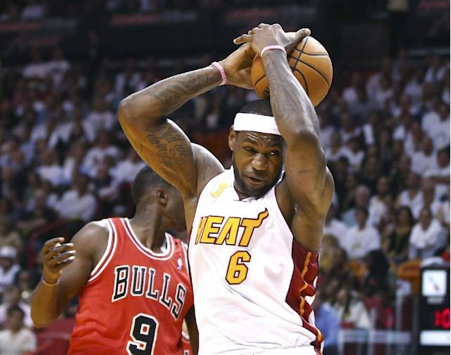 Miami Heat's LeBron James (6) loses control of the ball as Chicago Bulls' Luol Deng (9) defends during the first period of an NBA basketball game in Miami, Tuesday, Oct. 29, 2013. (AP Photo/J Pat Carter)