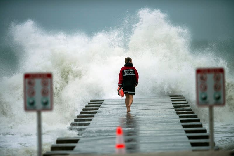 A lifeguard walks to the end of the jetty after closing it down to surfers before the arrival of Tropical Storm Eta in Bradenton Beach