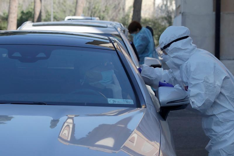 Medical staff of a mobile unit take samples from people in cars to test for Covid-19 at a drive-through position at the Santa Maria della Pieta' hospital complex, in Rome, Friday, April 3, 2020.